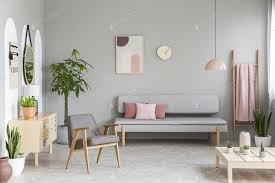sofa mit pastellrosa kissen in echtem foto grauen wohnzimmer foto bialasiewicz auf envato elements