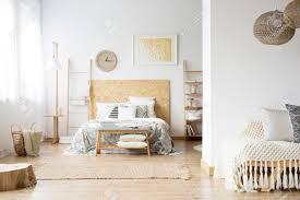 geräumiges böhmisches schlafzimmer mit holz decken und bett gegen eine wand mit gelber malerei und uhr