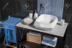detail eines modernen badezimmer mit waschbecken und zubehör badezimmerschrank und blauen fliesen im bad
