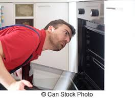 Worker Repairing The Oven In Kitchen