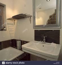 silver metallic mirror above white basin in small monochromatic