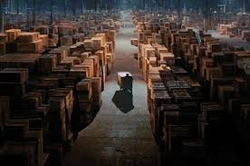 Scene Of Raiders The Lost Ark Where Some Nameless Government Worker Pushes Boxed Covenant Through A Giant Warehouse Filled With Crates