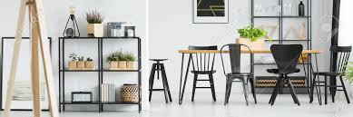 anlagen auf regal und schwarzen stühlen am speisetische im hellen esszimmer mit holzmöbeln