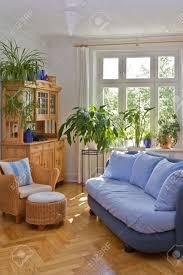 helles wohnzimmer im alten gebäude mit stuck sofa sessel hocker und antiken schrank in blau und warme farben