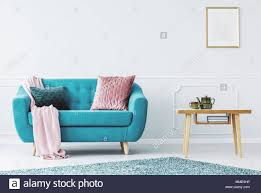 blaues sofa mit pastell rosa decke und zwei kissen im hellen