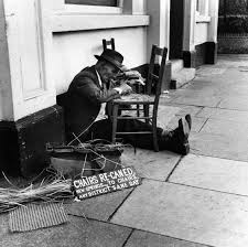 Re Caning Chairs London by A London Tradesman Repairs A Chair On The Street 1950s