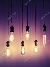 industrial style light bulbs on purple background stock photo
