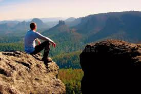 Download Young Man In Black Sportswear Is Sitting On Cliff Edge And Looking To Misty Valley