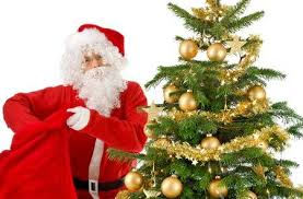 Santa Claus Beside A Christmas Tree With Gold Ornaments Looking Into The Camera And Reaching