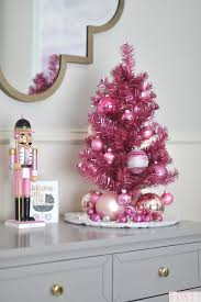 A Little Shiny Christmas Tree With Ornaments In Different Shades Of Pink