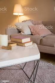 skandinavischen innenraum braune wand im wohnzimmer gemütliches zimmer komfortables zimmer rosa und graue kissen auf dem sofa le bücher und kerze