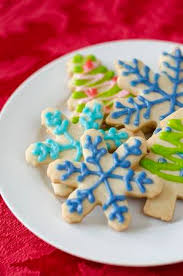 Snowflake And Christmas Tree Shaped Sugar Cookies Decorated With Icing On A White Plate Stock Photo