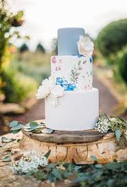A three tiered blue and white wedding cake decorated with white sugar flowers