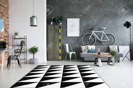 schwarzweiss teppich im geräumigen wohnzimmer mit arbeitsplatz und weißem fahrrad über grauem sofa