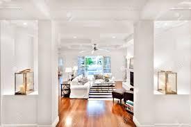 modernes wohnzimmer mit weißen wänden und säulen die sofas und schaufenster im freien umgeben