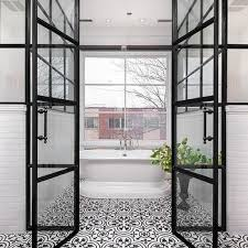 walk in shower with black and white quatrefoil cement tile shower