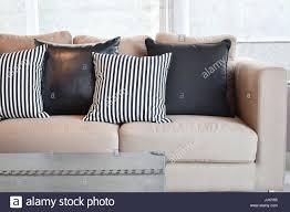 gestreifte und schwarze leder kissen samt beige sofa im