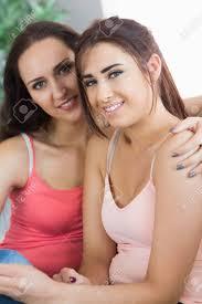 zwei schöne frauen lächelnd in die kamera während der sitzung in das wohnzimmer