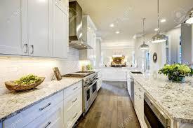 weiße küche design verfügt über große bar stil kücheninsel mit granit arbeitsplatte durch moderne pendelleuchten beleuchtet northwest usa
