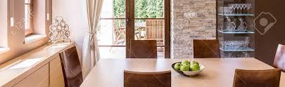 warme esszimmer mit massivholztisch und stühle offen für eine terrasse