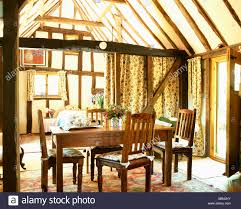 Antique Table And Chairs In Beamed Country Dining Room With Apex Ceiling Heavy Curtain Drawn Back To Show Entrance Hall