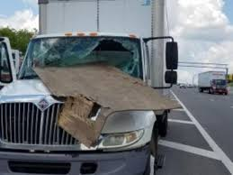 Flying Debris Loose Plywood Flyes Into Tractor Trailer Rig