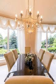 elegantes esszimmer mit großem tisch stühlen und kronleuchter