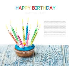 Birthday cupcake with burning candles on a white background Empty white space above and below for sample background and text
