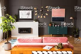 pflanze neben rosa in grau wohnzimmer interieur mit plakat über dem kamin echtes foto stockfoto und mehr bilder baum