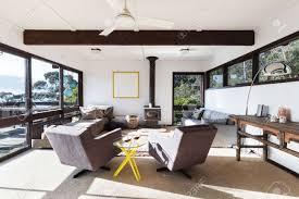 funky retro strandhaus wohnzimmer mit 70er jahre stil lehnstühlen und einem atemberaubenden blick