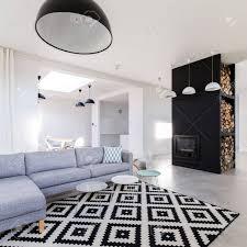 stilvolles grau weißes wohnzimmer mit gemütlichem sofa modernistischem kamin und gemustertem teppich