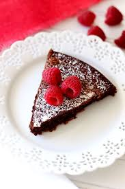 A slice of Flourless Chocolate Torte topped with powdered sugar and raspberries on a white lace