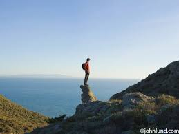 Man Standing On A Rocky Cliff Looking Out At The Vast Ocean