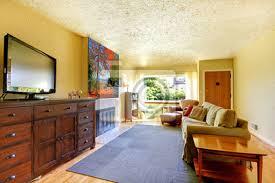 fototapete wohnzimmer mit grauem teppich gelbe wände und tv auf große kommode