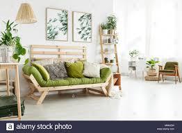 grün holz sofa mit vielen kissen in helles wohnzimmer