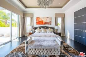 The Bedroom Features A Stylish Rug On Top Of Hardwood Flooring Tray Ceiling