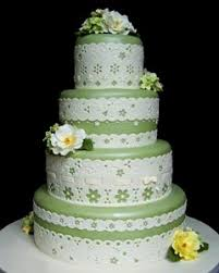 Four tier green and white lace wedding cake Decorated with yellow and white flowers From