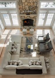 Awkward Living Room Layout With Fireplace by A Dramatic Floor To Ceiling Stone Fireplace Is The Focal Point In