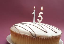 Iced 15th Birthday cake with burning number candles over a pink background with copyspace for your