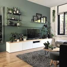 wohnzimmer mit weißem fernsehschrank und grüner wand