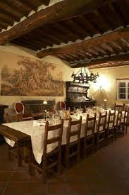 Tuscan Style Dining Room With Wooden Ceiling Beams And Wall Art Chandelier Sconce