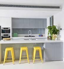 cuisine jaune et blanche trois tabourets tolix jaune dans une cuisine grise