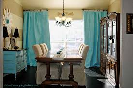 Turquoise Drapes Cabinetry And Chandelier Ornamentation Tie In Beautifully With The White Browns Of Dining Room Table Chair