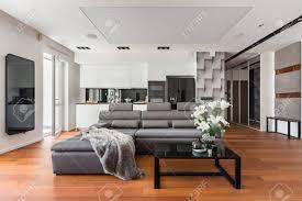 offenes wohnzimmer mit grauem sofa schwarzem couchtisch und küchenzeile