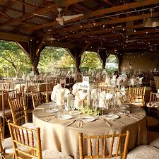 Rustic Country Wedding Reception Decorations With Exposed Beam Ceiling And Glass Lanterns On Round Tables