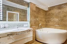 innere des stilvollen badezimmer in braunen und weißen farben mit abgerundeten keramik badewanne in der ecke des raumes und der große spiegel an wand