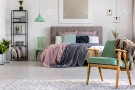 grüner hölzerner lehnsessel auf grauem teppich im schlafzimmerinnenraum mit len und malerei über bett