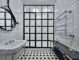 badezimmer mit wänden aus weißen fliesen es gibt weiße waschbecken schwarze spiegel dusche mit schwarzen trennwand aus glas quadrate und leuchtende