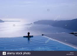 Female Silhouette In Infinity Pool On Cliff Edge Looking Out Over Blue Sea Santorini Greece Islands