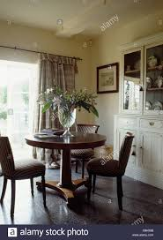 Upholstered Chairs And Victorian Table In Country Dining Room With Slate Flooring